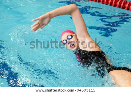 young girl swims  in the pool