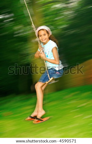 Young girl swinging fast on the rope swing tied to a tree. - stock photo