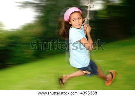 Young girl swinging fast on the rope swing tied to a tree, enjoying the outdoors. - stock photo