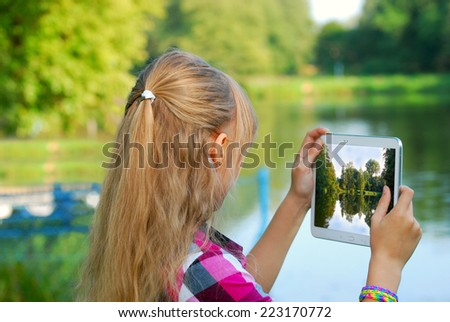young girl taking photo of the lake by tablet pc  on vacations - stock photo