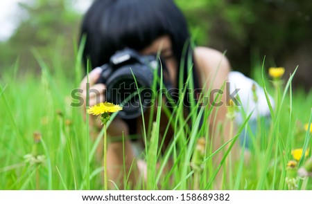 young girl taking picture of  dandelion in nature - stock photo