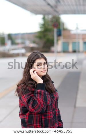Young girl talking on her cell phone at bus stop. Shallow depth of field. - stock photo