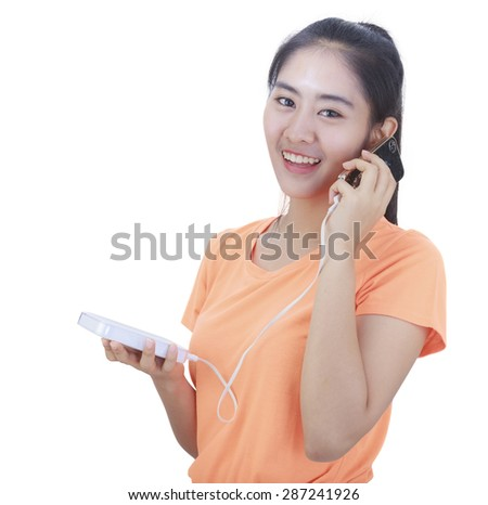 young girl talking smartphone and charging with power bank while in standby on hand - stock photo