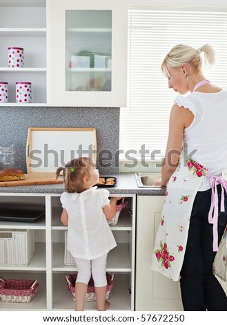 Young girl talking to her mother in kitchen - stock photo