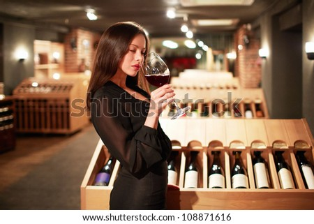 Young girl tastes the wine - stock photo