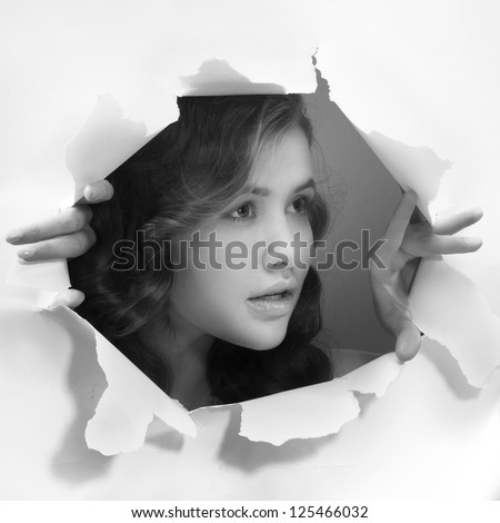 young girl tearing white paper wall breakthrough design element template - stock photo
