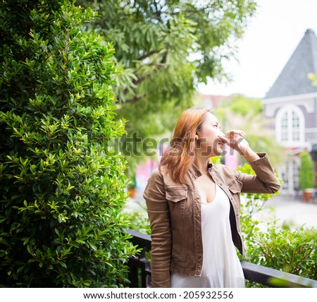 Young girl thinking and looking out in city's park - stock photo