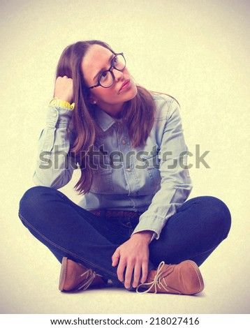 young girl thinking and sitting - stock photo