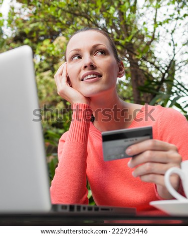 Young girl thinks about purchasing through the internet - stock photo