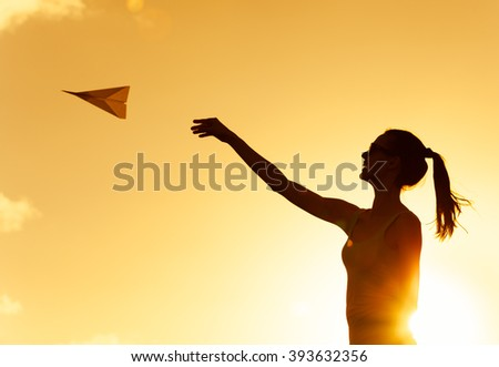 Young girl throwing a paper airplane.  - stock photo