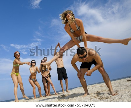 Young girl to jump across her boyfriend against joyful team of friends having fun at the beach - stock photo