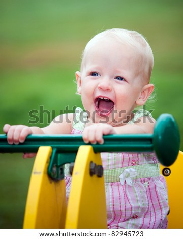Young girl toddler or kid playing on seesaw at playground outdoors at park. - stock photo