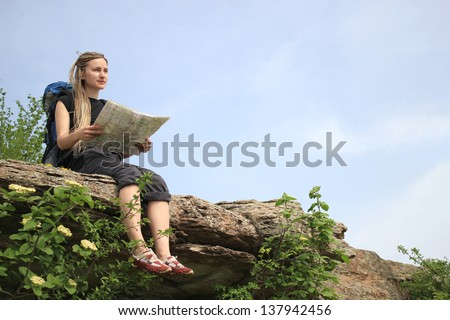 Young Girl Tourist with African Braids in Mountain read the Map on the Rock - stock photo