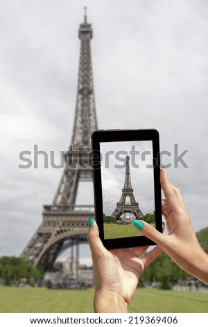 Young girl traveling and taken pictures Eiffel Tower, with tablet - stock photo