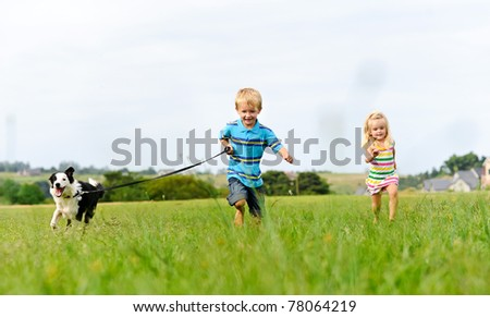 Young girl tries to catch up with her brother running ahead with their new puppy - stock photo