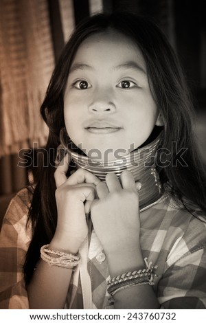 Young girl try to use  Karen Long Neck same as women in traditional hill tribe village also known as Kayan indigenous ethnic group. Famous tourist travel destination. - stock photo