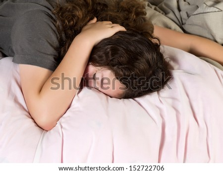 Young girl trying to wake up in the morning with hand over her head while lying in bed - stock photo