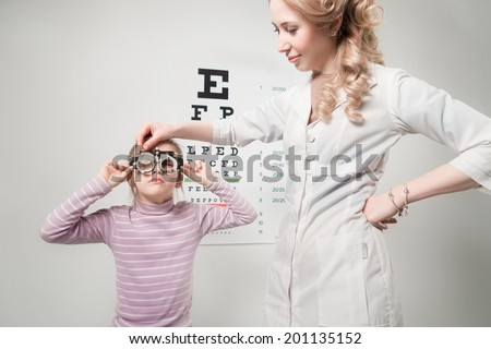 Young girl undergoing eye test with phoropter - stock photo