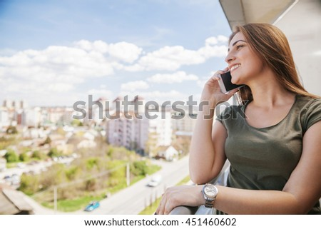 Young Girl Using A Smartphone On A Balcony - stock photo