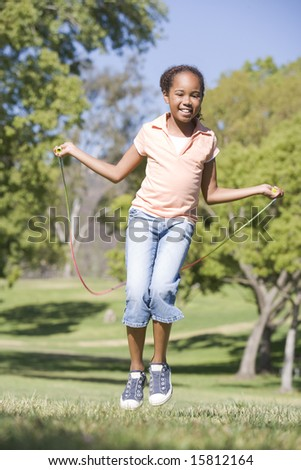 Young girl using skipping rope outdoors smiling - stock photo