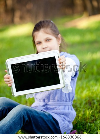 Young girl using tablet outdoor laying on grass - stock photo