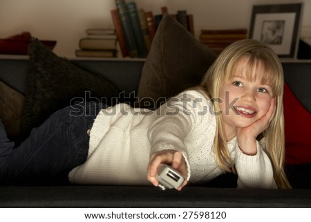 Young Girl Using Television Remote Control - stock photo