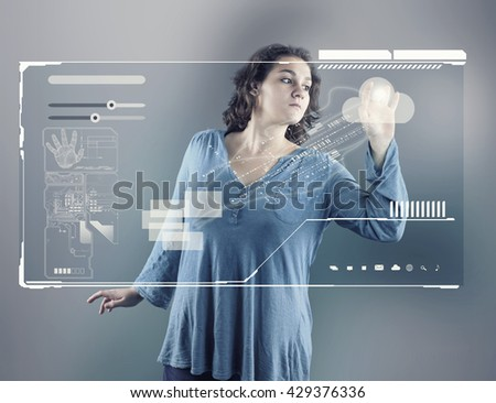 Young girl using virtual screen; checking database and identity on high tech technology - stock photo