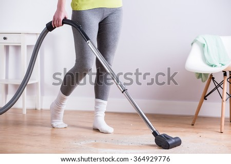 Young girl vacuuming dirty wooden parquet