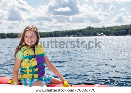 Young girl waiting for the boat to take her for a ride... - stock photo