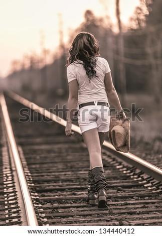 Young girl walking along railroad in white shorts - stock photo