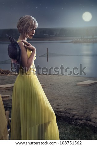 Young girl walking along the beach at night - stock photo