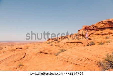 Young girl walking down the horse shoe bend cliffs at the Grand Canyon.