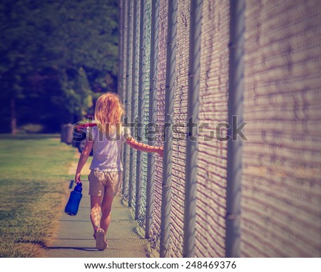 young girl walking dragging fingers along chain link fence during sunny afternoon with retro instagram filter - stock photo