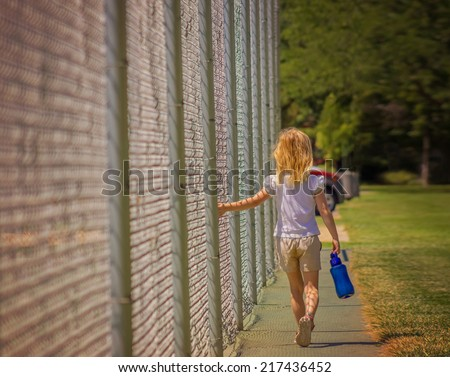 young girl walking dragging fingers along chain link fence during sunset or sunrise - stock photo