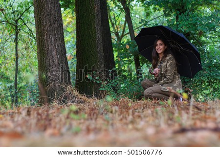 Young girl walking on a path in a forest a rainy day. She goes with an umbrella against the rain. The forest is very colorful.