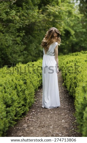 Young girl walking on an alley in the park - stock photo