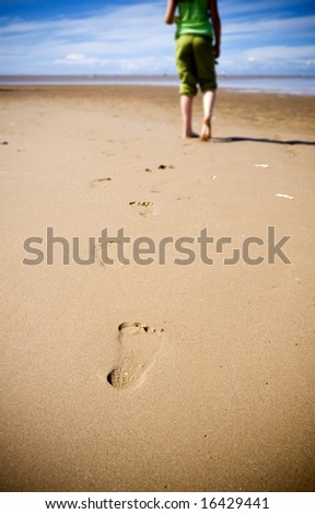 Young girl walking on the beach leaving footprints in the sand - stock photo