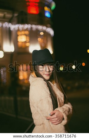 Young girl walks on a night city
