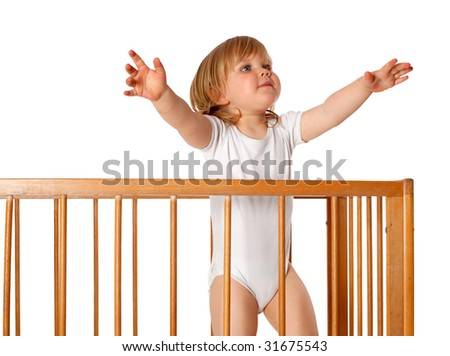 young girl wants to be taken out from cot - stock photo