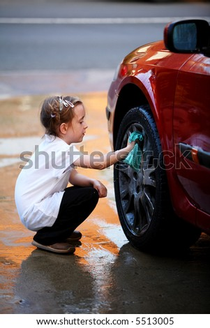 Young girl washing the wheel of a red car - stock photo