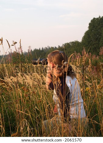 Young girl watches birds near the river, close-up - stock photo