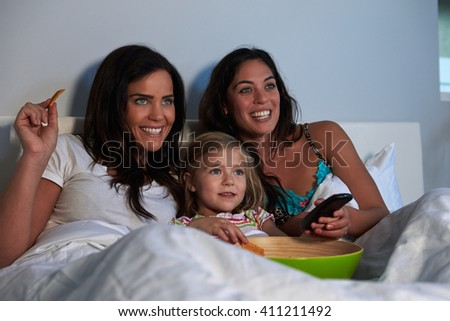 Young girl watching TV in bed with gay female parents - stock photo