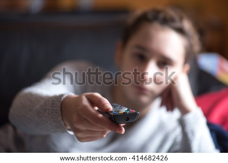 young girl watching TV with remote control in living home