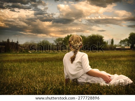 Young girl wearing a white dress sitting in a grassy pasture or prairie looking at sunset - stock photo