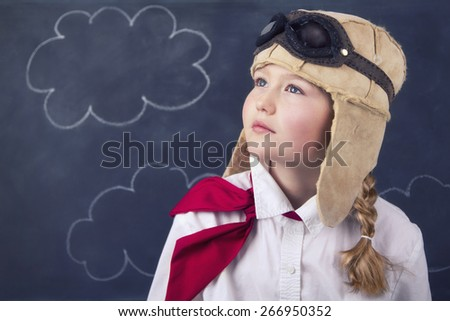 Young girl wearing aviator goggles and hat with chalk board and clouds in background