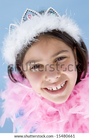 Young girl wearing crown and feather boa smiling - stock photo