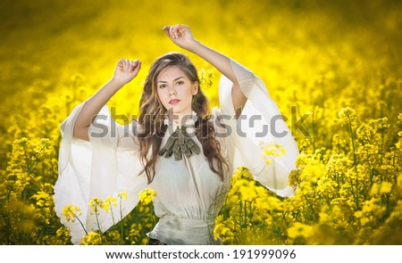 Young girl wearing elegant white blouse posing in canola field, outdoor shot. Portrait of beautiful long hair brunette with large transparent sleeves in bright yellow rapeseed field, spring scenery - stock photo