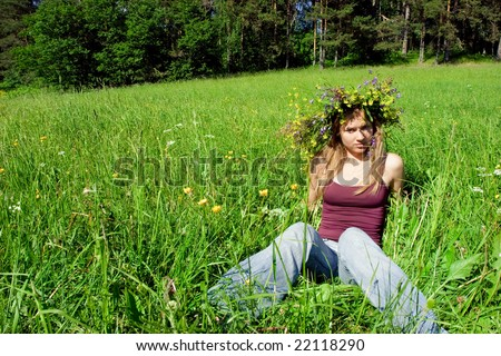 Young girl wearing flower wreath on summer forest meadow