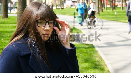 Young girl wearing glasses and waiting meet in park. Attractive woman sitting on bench enjoying life outdoors in spring city park. Happiness lifestyle people background. - stock photo