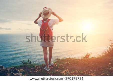 Young girl wearing hat and backpack looking far away at sunset near ocean (intentional sun glare and vintage color) - stock photo